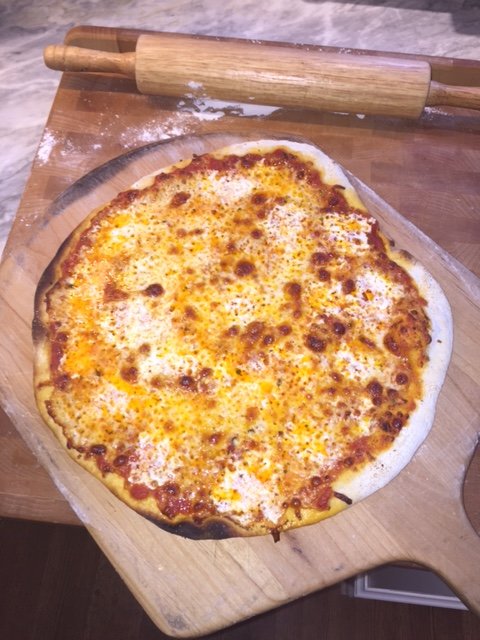Out of the oven, the pizza is resting before we dig in!
