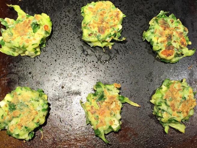 zucchini fritters are cooking on the other side