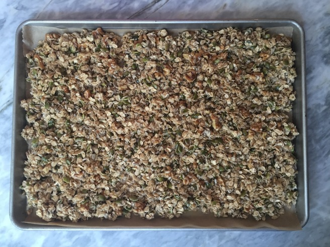 Wet granola ingredients on a cookie sheet, ready for the oven.