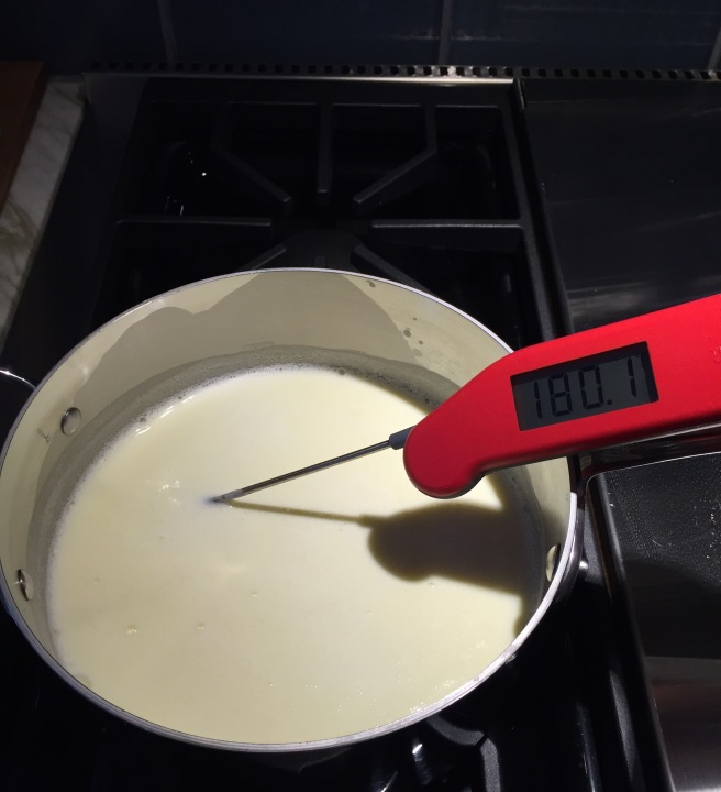 Milk and cream heating on the stove until it reaches 180°.
