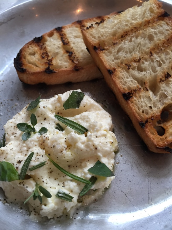 Homemade whipped ricotta sprinkled with herbs and served with grilled ciabatta.