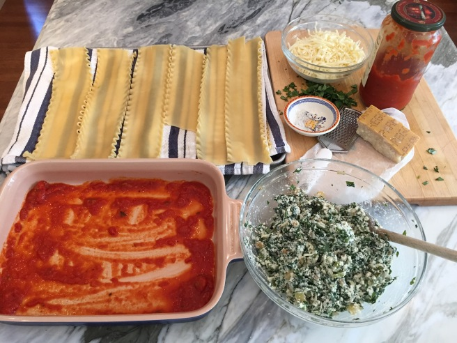 Lasagna roll up ingredients are out and ready for assembly, casserole dish, lasagne noodles, mozzarella cheese, parmesan cheese, filling, marinara sauce and salt.