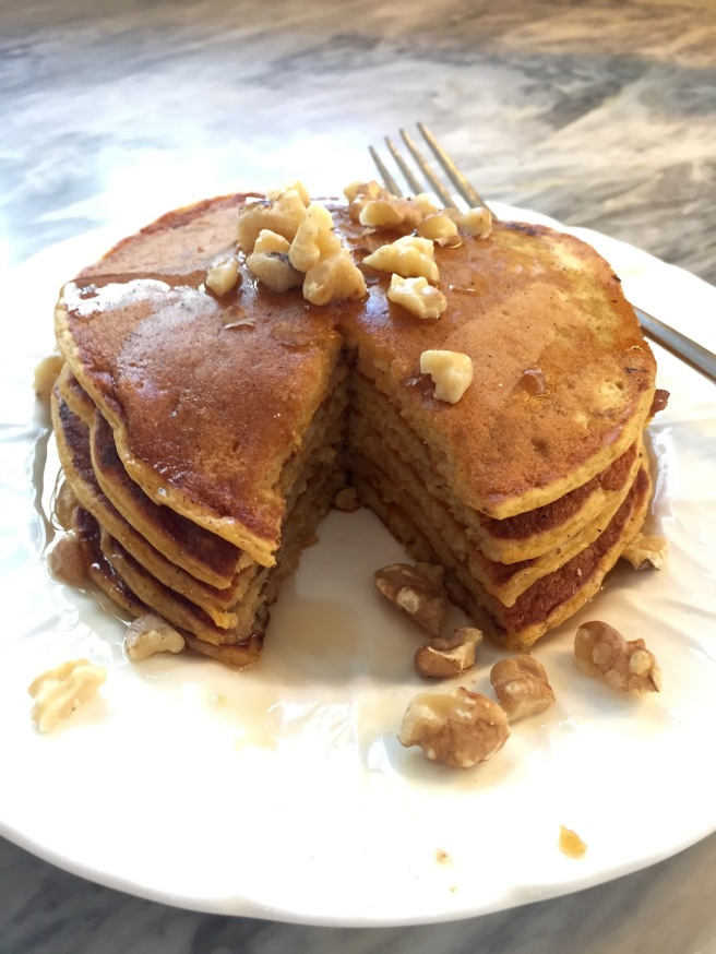 Pumpkin pancakes served with warm maple syrup and toasted walnuts.