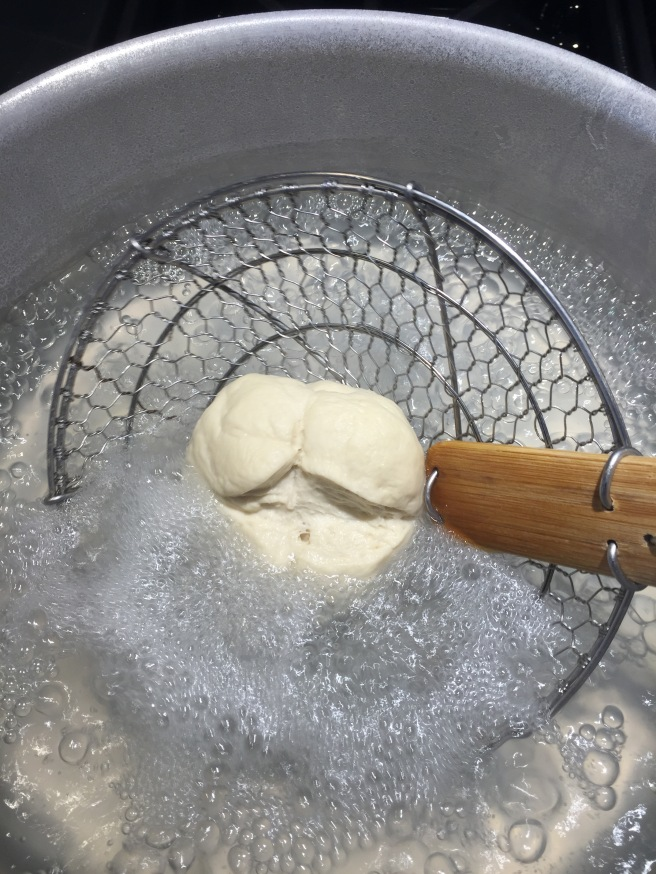 Dropping the pretzel bun into boiling water/baking soda mixture