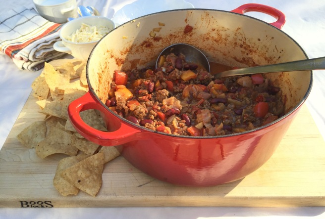 Chili con carne with tortilla chips, cheese, and sour cream.