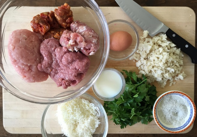 Meatball ingredients on a cutting board- ground turkey, hot italian sausage, sweet italian sausage, pecorino romano cheese, parmesan cheese, milk, egg, parsley, breadcrumbs, and salt