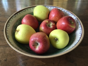 Braeburn and golden delicious apples in a bowl.