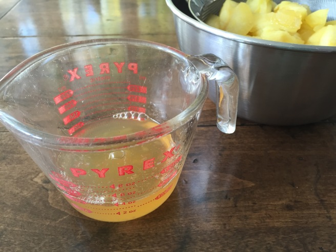 Apple syrup in measuring cup, with apples draining in sieve.