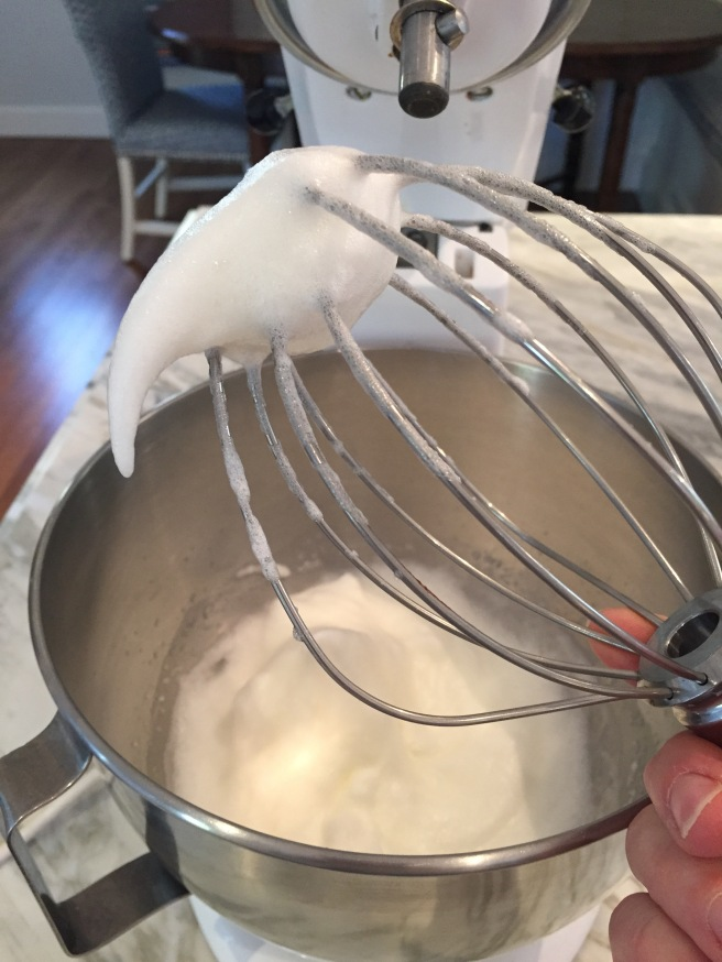 Soft peak egg whites on whisk.
