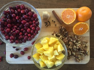 Cranberries, pineapple, walnuts, satsumas, cinnamon, cloves, allspice berries and ginger on a cutting board.