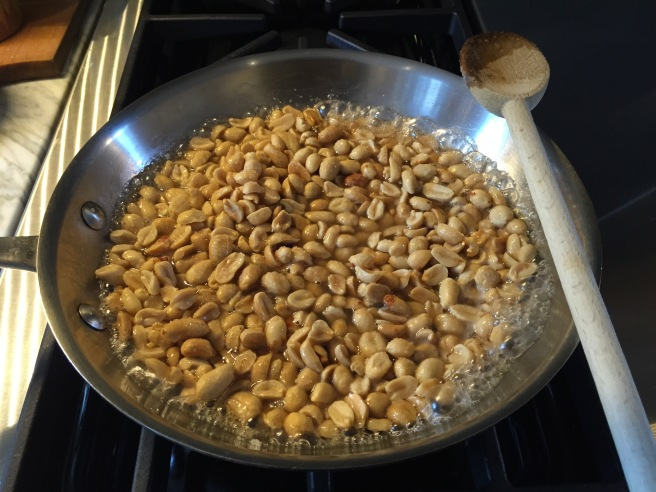Peanuts, sugar, and water bubbling away on stove top.