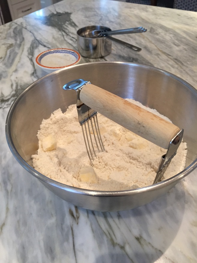 Pastry blender cutting butter into dry ingredients.