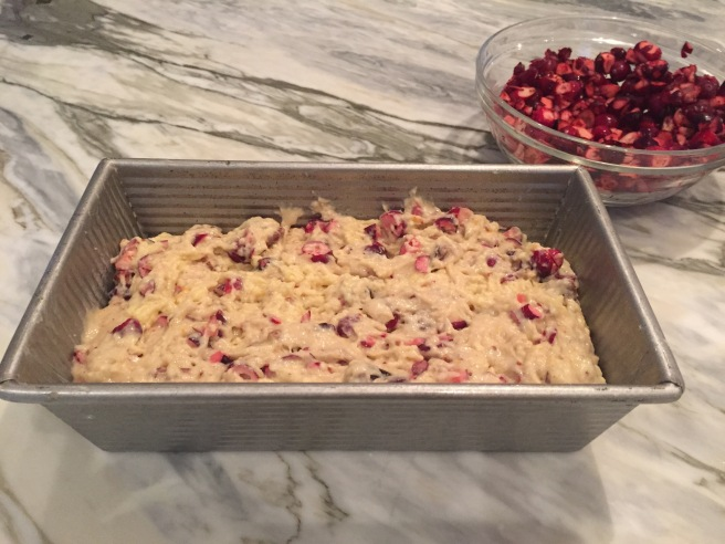 Cranberry Nut Bread batter in a greased loaf pan getting ready to go in the oven.