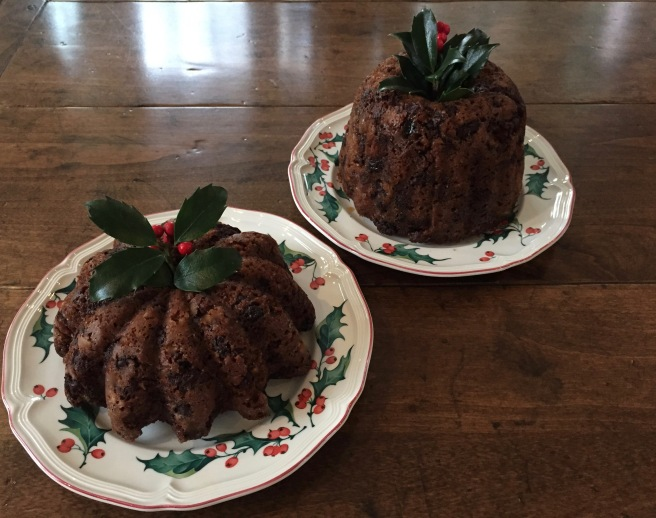 Two plum puddings decorated with holly sprigs.