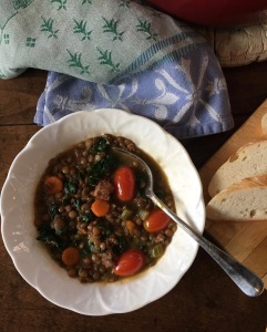 Individual bowl of lentil soup with sausage and kale.