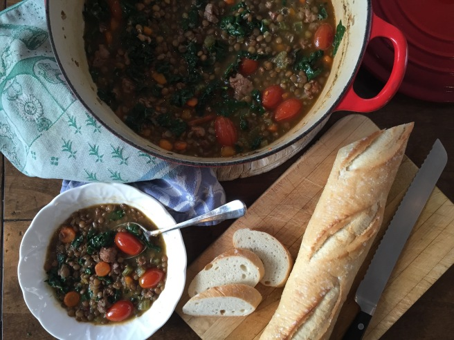 Serving lentil soup from dutch oven, along with baguette on a cutting board.