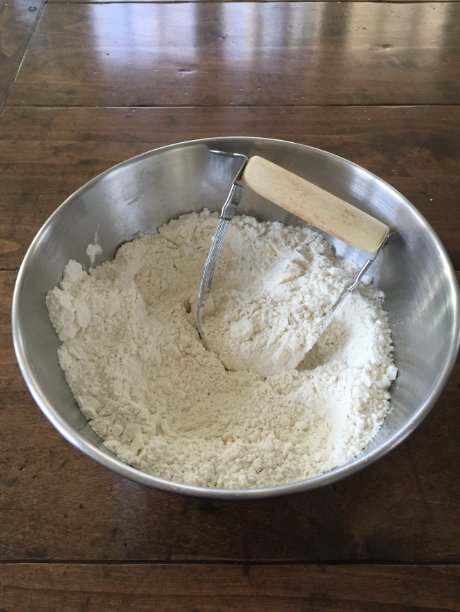 Using a pastry blender to cut butter into flour.