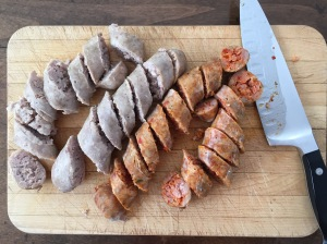 Sliced sausage on a cutting board with chef's knife