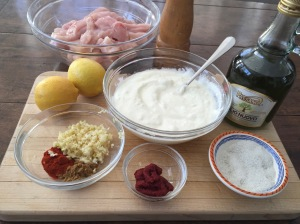 Shish Taouk ingredients on cutting board: ingredients: cubed chicken breast, plain yogurt, lemon juice, olive oil, garlic, smoked paprika, cumin, tomato paste, salt and pepper.