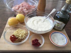 Shish Taouk ingredients on cutting board: ingredients: cubed chicken breast, plain yogurt, lemon juice, olive oil, garlic, smoked paprika, cumin, tomato paste, salt and pepper.