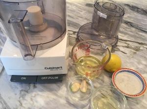 Food processor with ingredients for toum- garlic, lemon, salt, egg white, and canola oil.