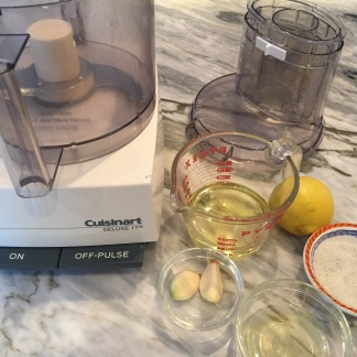 Food processor with ingredients for toum- garlic, lemon, salt, egg white, and canola oil.