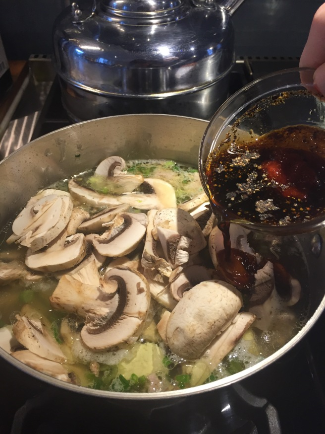 Adding sugar, vinegar, soy sauce, black pepper, sesame oil, and Sriracha to soup