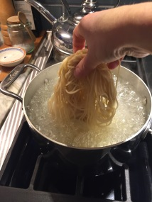 Dropping chinese noodles into boiling water
