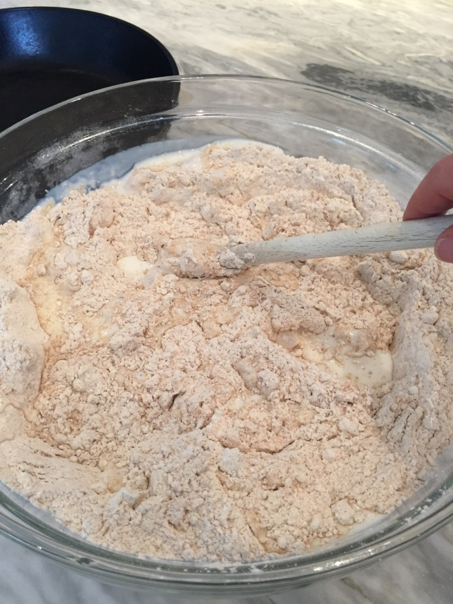 Mixing brown soda bread dough with a wooden spoon